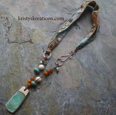 "ceramic pendant (by Summer Wind Arts), riverstone, jasper, Czech glass and turquoise beads, Irish waxed linen cording, solid copper metals (by me), and batik ribbons with sewn edges. Length is approx. 20"" and pendant is approx. 1.75"" in length."