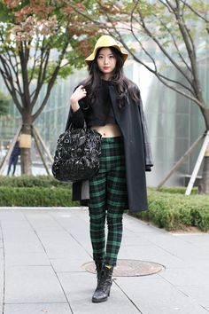 It takes a lot to make us covet a bucket hat; her slim-cut tartan trousers and sleek black coat are the perfect enticement.