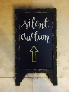Directional signage for a silent auction at a conference using Hobby Lobby chalkboards and white and gold metallic chalk markers #chalk #chalkboard #chalkmarker #diy #calligraphy #party #partysign #directionalchalkboard #event #eventsign #signage