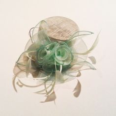 Pretty miniature top hat fascinator with tri-flower ribbons, crin bows and biot and quill feathers. $35