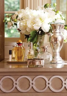 What I love on my dressing table.perfume bottles, silver chalise and flowers