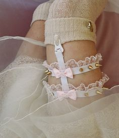 This item is only ONE garter. A white elastic garter made with metal screwback spikes, elastic, lace, bows and a garter clip. The elastic