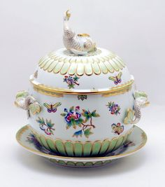"""DESCRIPTION: Large Herend covered tureen, round in shape with three dimensional dolphin handles and decorated with flowers and butterflies, base of tureen and top of lid with raised scallops, lid with dolphin finial, on matching underplate, bases marked """"Herend Hungary Handpainted"""
