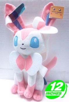 Pokemon Sylveon Plush  Quite simply one of the prettiest Pokemon, Sylveon is perfectly recreated in these toys complete with all of its pink and blue bows and ribbons. Give the fairy Eeveelution a new home today!  - Plush is approx 30 cm / 12 inches tall. - Brand new with tags. - Ages 6 & up.