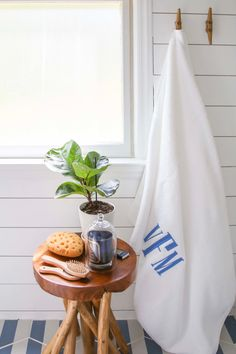This nautical kids bathroom is packed with small bathroom remodel ideas. These decorative details include monogrammed towels, painted shiplap, and greenery. The paint is Fresh Kicks by Clare. #bathroomideas #bathroomremodel #bathroomdecor #bathroominspo #shiplap #whitepaint #nauticalbathroom