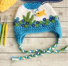Fishbowl Crochet Baby Hat Pattern | The buttons and fish on this crochet hat pattern are to die for, and the details of the braided tie perfectly bring it all together.
