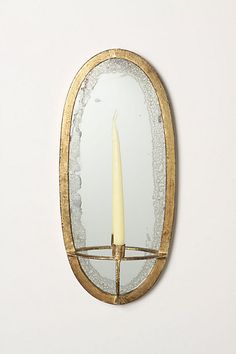 """I found it! It was on HGTV blog. I want 2 oval mirror taper candle sconces to flank a mirror in our dining room. Artemis Bow Mirror #anthropologie  DETAILS   Gleaming-yet-weathered arcs fit for an Olympian frame this taper holder-looking glass hybrid. Iron, gold leaf, glass   20""""H, 9""""W, 3.5""""D   Imported"""