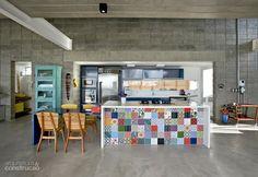 Numa base predominantemente cinza, com blocos de concreto aparente e piso de cimento queimado, a bancada da cozinha sobressai. Feita de alvenria, ela tem azulejos coloridos, tampo e laterais de Quartzo stone. Projeto de Bernardo Telles.