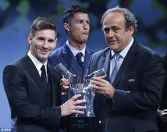 Lionel Messi (left) receives his award from Michel Platini (right) as Cristiano Ronaldo stands in the background