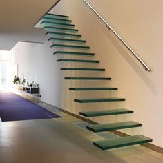 Floating Glass Staircase by EeStairs - hidden support system, with stair treads projecting straight out of the wall.