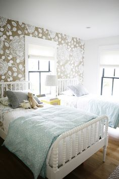 Adorable shared kids' room features white and taupe floral wallpaper on accent wall framing a pair of white twin Jenny Lind Beds dressed in gray fringed pillows and turquoise scroll duvets flanking shared yellow nightstand topped with crystal lamp topped with white plated lamp shade situated under window dressed in white roman shade.