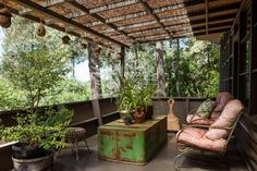 """On the porch off the kitchen is Dione's """"aviary real estate,"""" nests bought at Pier One that now house finches. The green table is an upside down cow's watering trough. For shade, Dione installed a bamboo garden fence roof."""