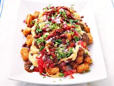Totchos (Tater Tot Nachos) With Cheese Sauce, Charred-Tomato Salsa, Chorizo, and Pickled Jalapeños