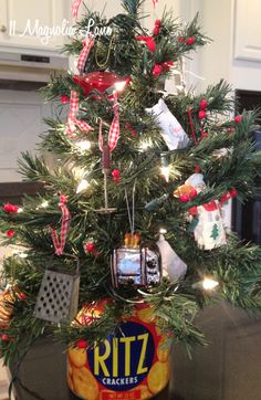 Kitchen Christmas tree at 11 Magnolia Lane - love the mini kitchen themed ornaments, such as a mixer, blender, cheese grater - so cute!  Tree is sitting in an old Ritz cracker tin.