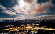 view of Canmore under a full moon from the summit of Lady Macdonald