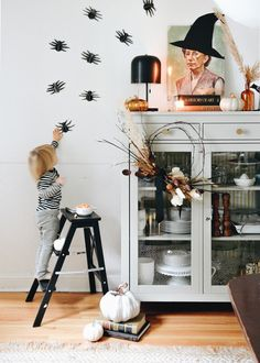 halloween decor, paper spiders on a white wall, toddler on step stool, china cabinet, pumpkins, wood floors