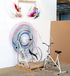 Joseph Griffith's drawing machine is driven by pedalling a stationary bicycle and turning handlebars, rotating coloured markers and moving them side to side against the wall. A participatory installation work, this device allows audience members to contribute to the drawing over time.