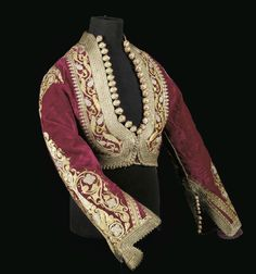 A LADY'S JACKET OF RED VELVET   TUNISIA, 19TH CENTURY   the deep red velvet ground densely embroidered in gilt thread, with knotted cylindrical, coral bead tipped decorative buttons