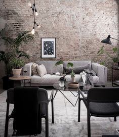 Modern industrial style loft styled by Emma Fischer | Red brick wall and matte black light pendant adds an industrial edge | the grey velvet sofa is an IKEA Nockeby sofa with a Bemz slipcover in Zinc grey zaragoza velvet