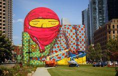 """The Giant of Boston (El gigante de Boston)  Artista: Os Gemeos Ubicación: Boston, E.U Mes: Agosto  A pesar de la molestia de algunos bostonianos por este mural a raíz de la idea que surgió de la representación de  un """"terrorista"""" (su palabra), este mural se ha convertido en un punto de referencia temporal en la ciudad. A menudo, las pequeñas obras de Os Gemeos son más interesantes que su serie gigante, pero éste sólo encaja en el espacio tan perfectamente."""