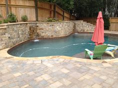 Stacked stone wall pool with #Sedona Red #PebbleTec