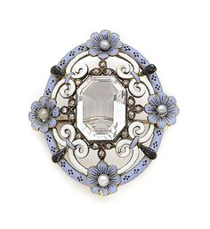 A rock crystal, enamel, seed pearl and diamond brooch, circa 1880. The cut-cornered step-cut rock crystal within a scrolling openwork surround of blue, black and white enamel, highlighted at the cardinal points with seed pearl buds, and accented with rose-cut diamonds, length 4.5cm