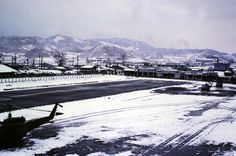 Dongducheon:  South extended runway at Alpha 220--Airfield for Camp Casey.  The buildings on the other side are shops in Dongducheon.  1973