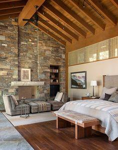 paredes decoradas, dormitorio con chimenea, techo triangular con vigas de madera, pared de piedra con chimenea, cama doble, sillones