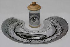 L'artiste hongrois István Orosz dessine ou peint des images distordues en anamorphoses qui se dévoilent lorsque l'on pose un cylindre en métal poli dessus et que l'oeuvre se réfléchit sur sa surface.