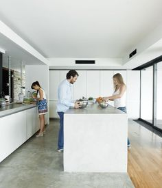 Alexia, Achilleas, and friend Fotini prepare lunch in the kitchen, outfitted with cabinets by Zeyko.  Concrete floor.