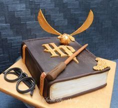 I really get nervous when I have to make any kiddy themed cakes and when I was asked to make a Harry Potter themed cake with minimum Fondant ,I was in a fix .To get a clean finish to look like a book with very little fondant was a challenge but I. Gateau Harry Potter, Cumpleaños Harry Potter, Harry Potter Birthday Cake, Harry Potter Book Cake, Harry Potter Enfants, Cupcakes Decorados, Creative Cakes, Themed Cakes, Party Cakes