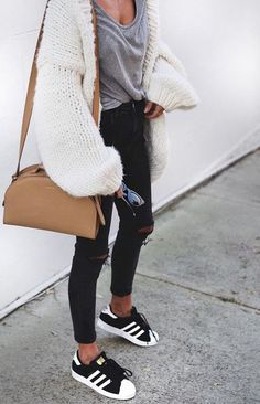 Un look d'automne avec un skinny déchiré, des baskets et un gilet en maille XXL