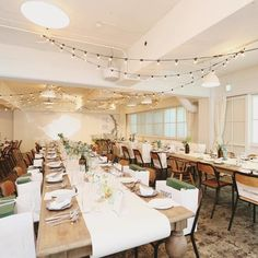 """披露宴会場全体的にはシンプルに。「ドレスとブーケが引き立つようにしたかった」とのこと。天井にはご新婦さまが絶対つけたかった電飾を飾りました。  優しい木の温もりがあるテーブルと椅子、電飾の灯り。会場装花へのこだわりは、""""結婚式らしいきっちりとしたものではなく、かといって森っぽい感じでもない""""やりすぎず、かといって省きすぎず、調度いいバランスのとれたオシャレな空間に仕上がっています。"""