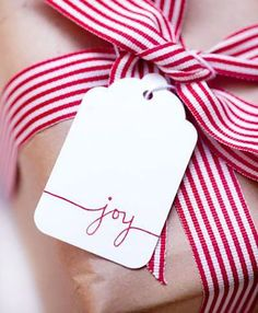 """red and white striped ribbon, white tag stitched with """"joy"""" to decorate brown wrapping paper for Christmas"""