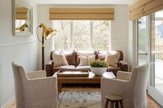 Chic cottage sunroom boasts off white paint on upper walls and beadboard trim on lower walls lined with a cognac leather 3 seat cushion accented with vintage French burlap sack pillows facing a pair of natural linen slipcovered chairs across from a farmhouse coffee table illuminated by a vintage Hollywood floor lamp.