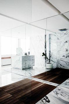 la salle de bain en marbre blanc gris et sol en planchers en bois foncé