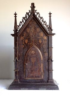 Gothic Reliquary cabinet from an Indo-Portuguese church in South India. Looks like a small Cathedral. This piece has an array of spiritual symbols on it, including a metal crucifix embedded in the top, an all seeing eye, a dove, grape leaves, a sunburst, roses, wheat, and a