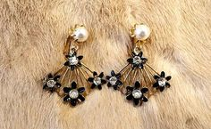 """Vtg Gold Filigree Oriental Fan Earrings - Rhinestones - Pearls - Vintage Clip On Back 60s    These lovely vintage earrings feature gold tone filigree fan shapes with little black enamel flowers and rhinestones.  They dangle from a caged faux pearl at the top.  Hinged clip backs, each earring measures 1 5/8"""" high.    I ship within one day of payment, usually same day, via USPS first class shipping, and I gladly combine shipping to save you money, contact me if you are purchasing multiple…"""