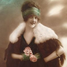 This young lady has beautiful hair that she is wearing in the latest style  of the roaring '20's. It is held in place by a wide green headband..