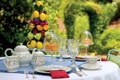 Cheery linens and an abundance of fresh flowers and fruit complement the colorful motifs of the china.