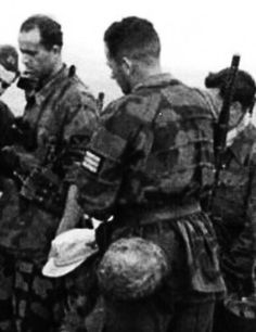 """Italian SS """"Debica"""" wearing Italian camo smock and camo smeared helmet. Below to his left can be observed a kneeling legionere with a tropical type m43 hat with eagle and skull."""