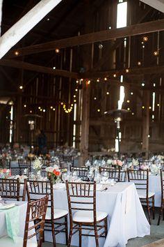The inside of a romantic barn wedding reception | @stewartuy | Brides.com