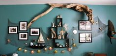 One piece of driftwood was too big for the basket....  so it found a home on the wall in our bedroom.  I draped fish netting on the wall and then hung my wall grouping over it.  I also added glass float lights to the bottom of the netting.