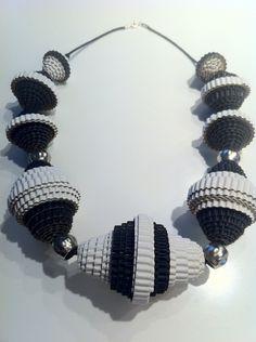 Silver è una collana realizzata con cartone ondulato nero e argento e con palle di argentone di diverse dimensioni. I colori del cartone e del cordoncino sono personalizzabili così come la lunghezza della collana stessa. Infine è trattata con uno spray impermeabilizzante.