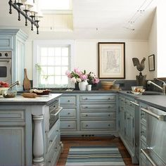 Never thought of blue cabinets --   add blue patina with French blue-painted cabinets gain the look of age with a distressed texture and a taupe glaze that clings to their door and drawer fronts, turned legs, and crown molding. Concrete countertops and stainless-steel appliances blend into the soothing blue background. A richly stained hardwood floor adds warmth underfoot.