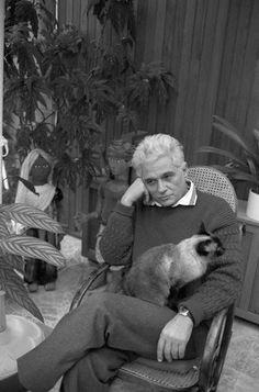 Postmodern French philosopher Jacques Derrida with his Siamese cat. Neither looks joyful. But then again, it's Derrida. Jacques Derrida wrote extensively of the feline gaze in an essay titled 'The Animal That Therefore I Am' Jaques Derrida, I Love Cats, Cool Cats, Men With Cats, Celebrities With Cats, Son Chat, Gatos Cats, Cat Logo, Cat People