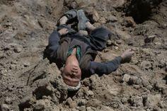 大規模な地滑りが発生したアフガニスタン北東部バダフシャン(Badakhshan)州のアーブバリーク(Aab Bareek)村で、土砂の上で悲しんでいる、孤児になった子ども(2014年5月5日撮影)。(c)AFP=時事/AFPBB News