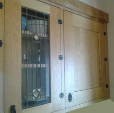 Custom cabinets in quartersawn white oak with inset stained glass doors and antique surface-mounted clover hinges made for a 1928 Craftsman four-square kitchen restoration.