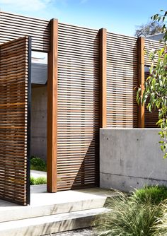 Designed by Acre - Munro Street. www.acre.com.au Photo by Derek Swalwell. Construction by Powda. Architect: Planned Living Architects. Entry with operable timber screen, off form concrete wall and coastal plant palette