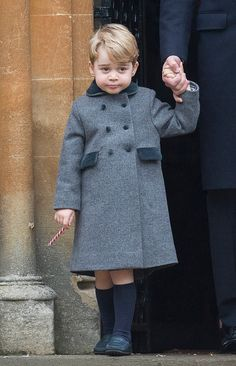 Prince George wearing double-breasted wool coat features velvet detail on the buttons, collar and side pockets. His warm coat was accompanied by his trademark look of socks pulled high.